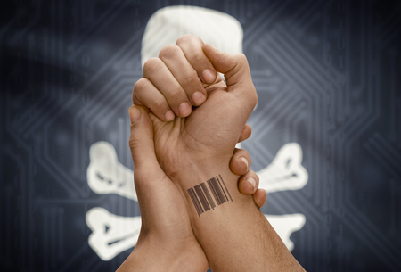 piracy: Barcode ID number tattoo on wrist of dark skinned person and flag on background - Jolly Roger flag - symbol of piracy