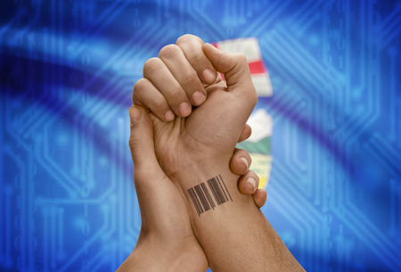 dark skin: Barcode ID number tatoo on wrist of dark skin person and Canadian province flag on background - Alberta