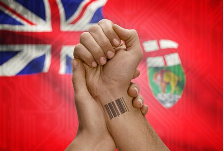 tatoo: Barcode ID number tatoo on wrist of dark skin person and Canadian province flag on background - Manitoba