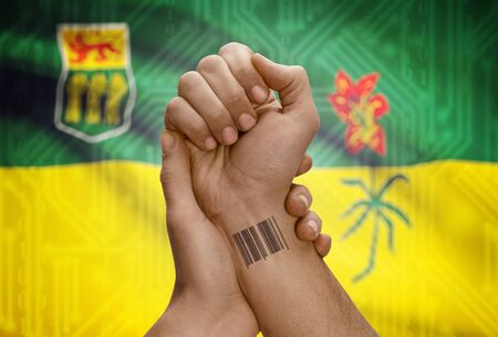 Barcode ID number tatoo on wrist of dark skin person and Canadian province flag on background - Saskatchewan Stock Photo