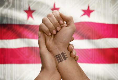district of columbia: Barcode ID number tattoo on wrist of dark skinned person and USA states flag on background - District of Columbia