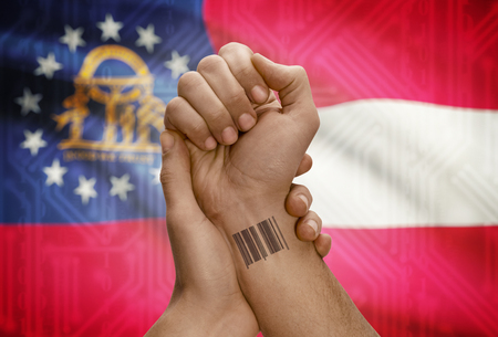 dark skinned: Barcode ID number tattoo on wrist of dark skinned person and USA states flag on background - Georgia