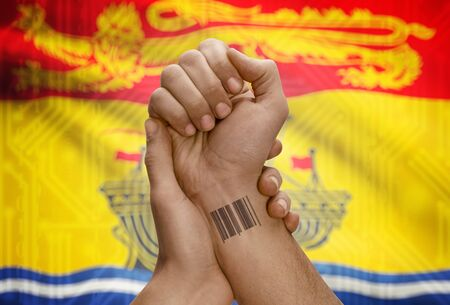 tatoo: Barcode ID number tatoo on wrist of dark skin person and Canadian province flag on background - New Brunswick