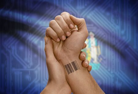 dark skinned: Barcode ID number tattoo on wrist of dark skinned person and USA states flag on background - Maine