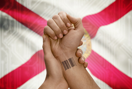 floridian: Barcode ID number tattoo on wrist of dark skinned person and USA states flag on background - Florida