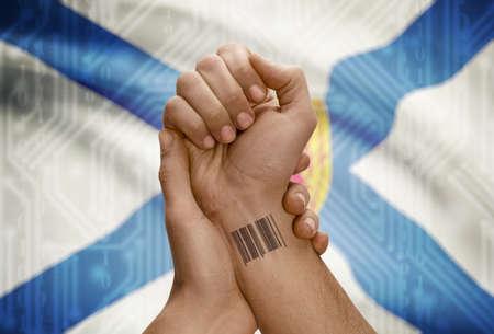 tatoo: Barcode ID number tatoo on wrist of dark skin person and Canadian province flag on background - Nova Scotia