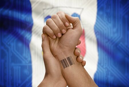 tatoo: Barcode ID number tatoo on wrist of dark skin person and Canadian province flag on background - Northwest Territories