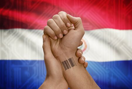 dark skinned: Barcode ID number tattoo on wrist of dark skinned person and national flag on background - Paraguay