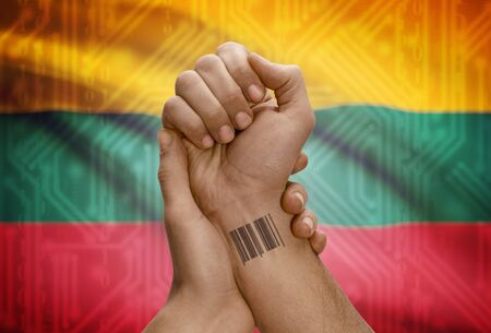 dark skinned: Barcode ID number tattoo on wrist of dark skinned person and national flag on background - Lithuania