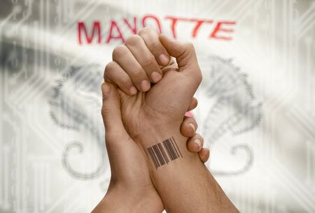 mayotte: Barcode ID number tattoo on wrist of dark skinned person and national flag on background - Mayotte Stock Photo