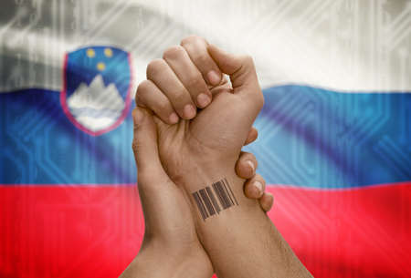 dark skinned: Barcode ID number tattoo on wrist of dark skinned person and national flag on background - Slovenia