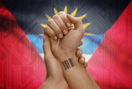 dark skinned: Barcode ID number tattoo on wrist of dark skinned person and national flag on background - Antigua and Barbuda