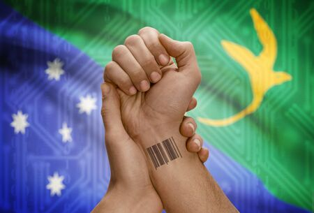 christmas tattoo: Barcode ID number tattoo on wrist of dark skinned person and national flag on background - Christmas Island