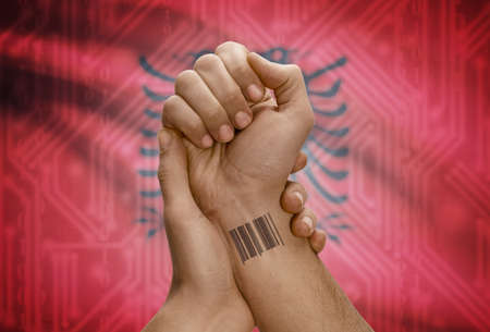 dark skinned: Barcode ID number tattoo on wrist of dark skinned person and national flag on background - Albania Stock Photo