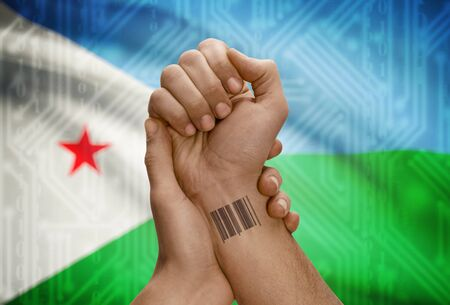 dark skinned: Barcode ID number tattoo on wrist of dark skinned person and national flag on background - Djibouti