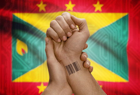 dark skinned: Barcode ID number tattoo on wrist of dark skinned person and national flag on background - Grenada