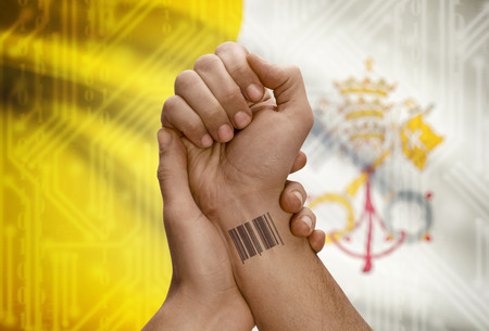 dark skinned: Barcode ID number tattoo on wrist of dark skinned person and national flag on background - Vatican City State Stock Photo