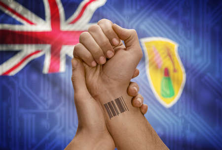 dark skinned: Barcode ID number tattoo on wrist of dark skinned person and national flag on background - Turks and Caicos Islands