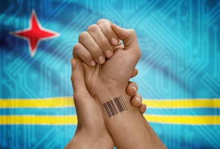 dark skinned: Barcode ID number tattoo on wrist of dark skinned person and national flag on background - Aruba
