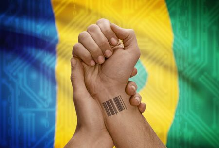 dark skinned: Barcode ID number tattoo on wrist of dark skinned person and national flag on background - Saint Vincent and the Grenadines