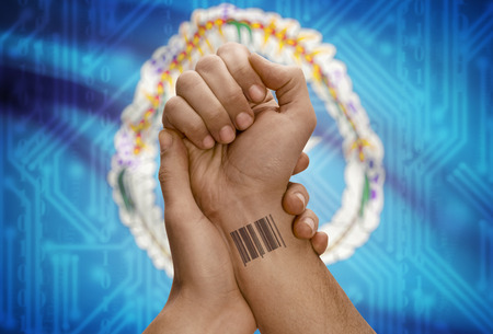 mariana: Barcode ID number tattoo on wrist of dark skinned person and national flag on background - Northern Mariana Islands