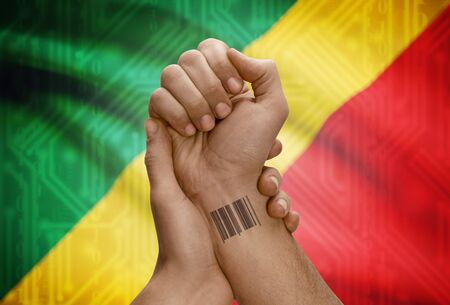 dark skinned: Barcode ID number tattoo on wrist of dark skinned person and national flag on background - Congo-Brazzaville
