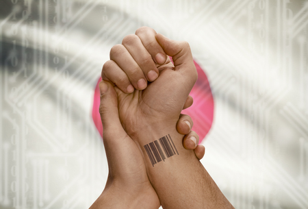 codigo barras: C�digo de barras de identificaci�n n�mero de tatuaje en la mu�eca de la persona de piel oscura y la bandera nacional en el fondo - Jap�n