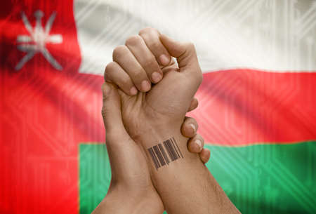 dark skinned: Barcode ID number tattoo on wrist of dark skinned person and national flag on background - Oman