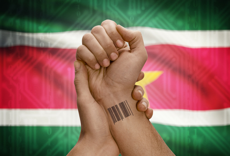 dark skinned: Barcode ID number tattoo on wrist of dark skinned person and national flag on background - Suriname Stock Photo