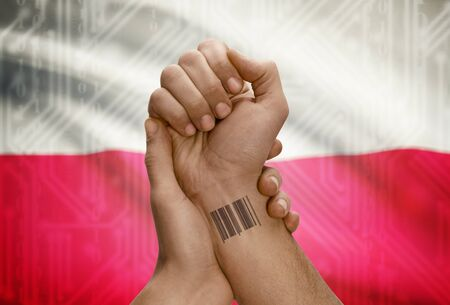 dark skinned: Barcode ID number tattoo on wrist of dark skinned person and national flag on background - Poland