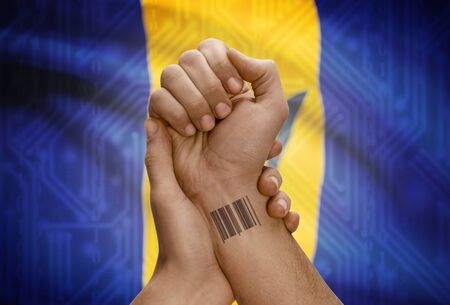 barbadian: Barcode ID number tattoo on wrist of dark skinned person and national flag on background - Barbados