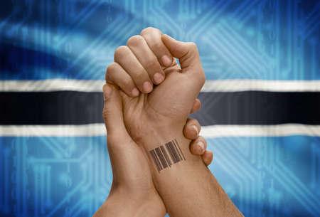 botswanan: Barcode ID number tattoo on wrist of dark skinned person and national flag on background - Botswana