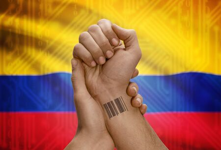 dark skinned: Barcode ID number tattoo on wrist of dark skinned person and national flag on background - Colombia