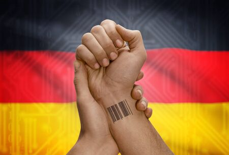 dark skinned: Barcode ID number tattoo on wrist of dark skinned person and national flag on background - Germany Stock Photo