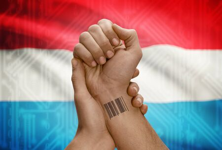 dark skinned: Barcode ID number tattoo on wrist of dark skinned person and national flag on background - Luxembourg Stock Photo