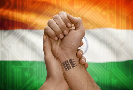 dark skinned: Barcode ID number tattoo on wrist of dark skinned person and national flag on background - India Stock Photo