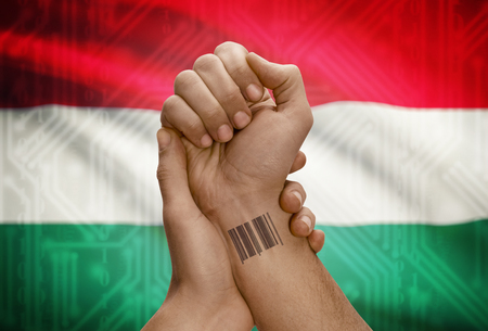 dark skinned: Barcode ID number tattoo on wrist of dark skinned person and national flag on background - Hungary
