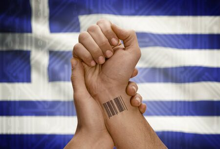dark skinned: Barcode ID number tattoo on wrist of dark skinned person and national flag on background - Greece