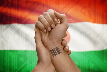 dark skinned: Barcode ID number tattoo on wrist of dark skinned person and national flag on background - Niger Stock Photo