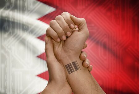 dark skinned: Barcode ID number tattoo on wrist of dark skinned person and national flag on background - Bahrain Stock Photo
