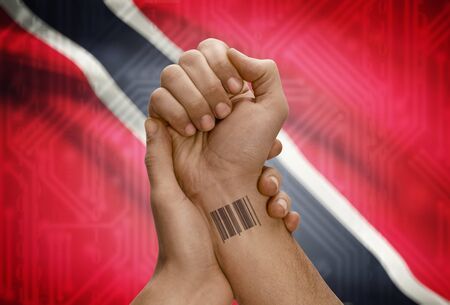 national flag trinidad and tobago: Barcode ID number tattoo on wrist of dark skinned person and national flag on background - Trinidad and Tobago Stock Photo