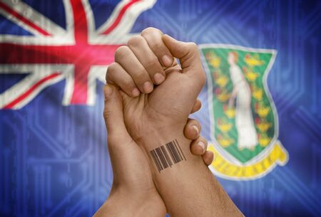 virgin islands: Barcode ID number tattoo on wrist of dark skinned person and national flag on background - British Virgin Islands