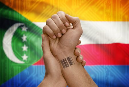 dark skinned: Barcode ID number tattoo on wrist of dark skinned person and national flag on background - Comoros
