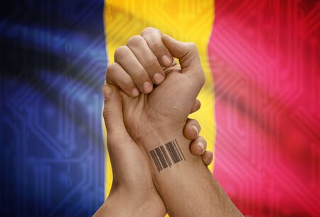 dark skinned: Barcode ID number tattoo on wrist of dark skinned person and national flag on background - Chad