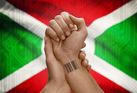 dark skinned: Barcode ID number tattoo on wrist of dark skinned person and national flag on background - Burundi