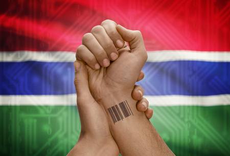 dark skinned: Barcode ID number tattoo on wrist of dark skinned person and national flag on background - Gambia
