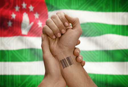 dark skinned: Barcode ID number tattoo on wrist of dark skinned person and national flag on background - Abkhazia Stock Photo