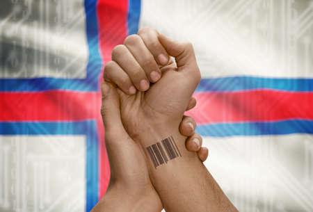 dark skinned: Barcode ID number tattoo on wrist of dark skinned person and national flag on background - Faroe Islands