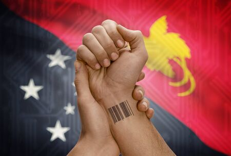 papua new guinea: Barcode ID number tattoo on wrist of dark skinned person and national flag on background - Papua New Guinea