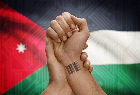 dark skinned: Barcode ID number tattoo on wrist of dark skinned person and national flag on background - Jordan Stock Photo
